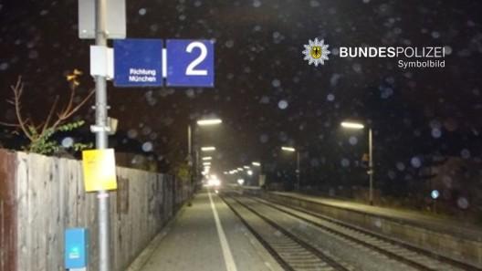 Zwei Männer (Deutsche) bewerfen sich im Gleisbett mit Schottersteinen