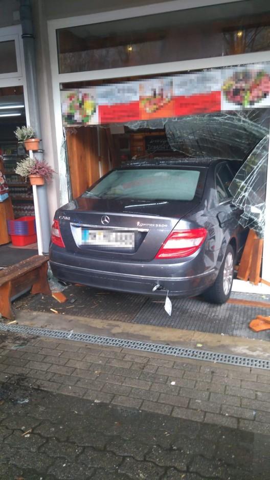 Auto fährt in Schaufensterscheibe
