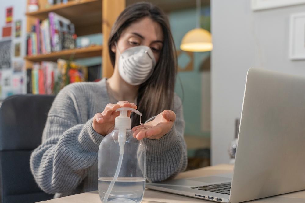 Geschäftsfrau, die von zu Hause aus arbeitet und eine Schutzmaske trägt